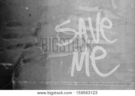 Save me message. Request for help written in water fogged glass.