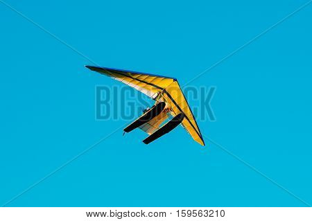 Motorized Hang Glider Flying On Blue Clear Sunny Sky Background.
