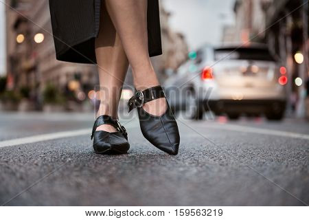Female feet wear elegant leather shoes. Woman feet wearing high-heels on city street.