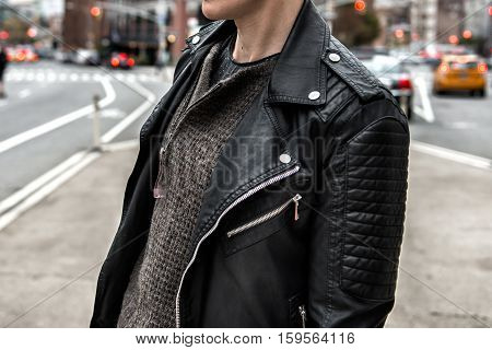 Men`s fashion concept. Stylish man wearing black leather jacket and walking on city street