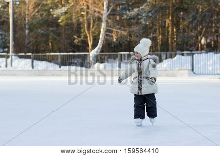 A child on a cold day in a warm jacket and hat learning to skate.