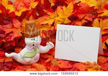 Halloween Ghostly Boo Scene Some fall leaves and white Halloween Friendly Ghost with a blank greeting card with copy-space for your message