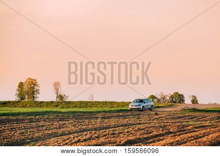 Gomel, Belarus - May 04, 2016: Volkswagen Polo Car Sedan Parking On Wheat Field. Sunset Sunrise Yellow Color Sky On A Background In Sunny Evening.