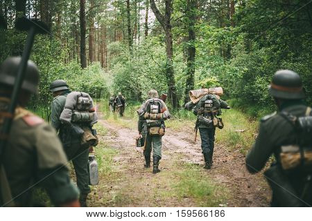 Group Of Unidentified Re-enactors Dressed As German Soldiers Marching Along Forest Road. Summer Season.