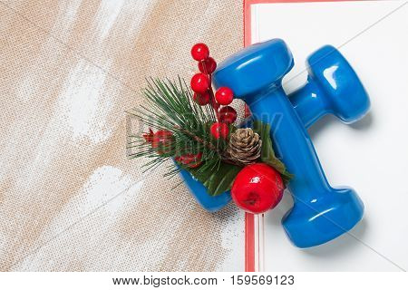 Christmas sport composition with dumbbells red gift box red berries green spruce on plywood background. Concept christmas special for healthy lifestyle and sport.
