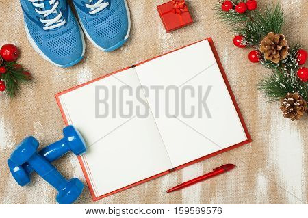 Christmas sport composition with blue sport shoes blue dumbbells red notebook red small gift box red pen and spruce branch with red berries and cones. Concept christmas special for healthy lifestyle and sport. Flat lay horizontal orientation.