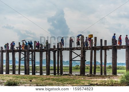 MANDALAY, MYANMAR - 13 OCTOBER 2016: People crossing U-Bein bridge which spans the Taungthaman lake near Amarapura. It is the oldest and longest teakwood bridge in the world