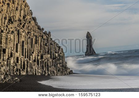 Reynisdranger, basalt sea stacks with the wave and black sand beach near the small village Vik i Myrdal in the south of Iceland