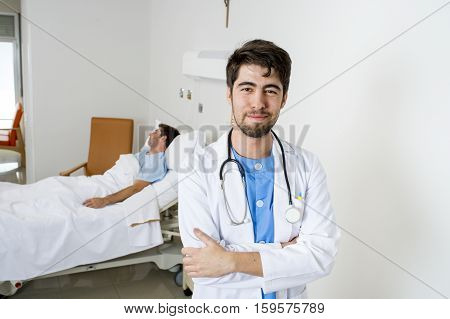 young happy and confident doctor posing in corporate portrait at hospital bedroom with sick patient lying in bed on the background in health care and medical attention concept