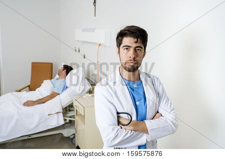 young doctor looking serious and worried posing in corporate portrait at hospital bedroom with sick patient lying in bed on the background in health care and medical attention concept