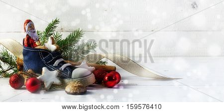 Childrens shoe filled with sweets cookies and christmas decoration for Nicholas day on the 6th December in Germany in front of white rustic wood with copy space panorama selective focus