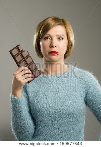 young cute woman holding big chocolate bar with mouth stains and guilty face expression in sugar addiction and ignoring diet concept isolated on grey background