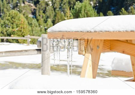 A picnic table covered in snow with an icicle shallow depth of field