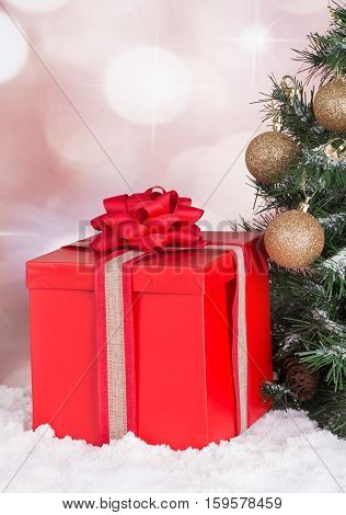 Red gift box next to a Christmas tree with a colorful background