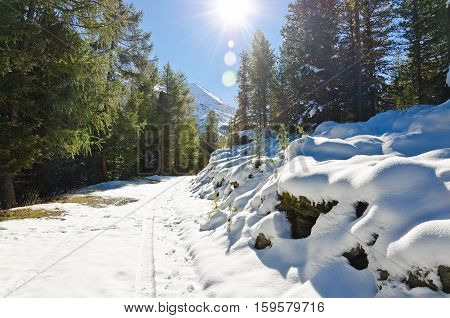 Snowy mountain road in the Alps with a bright sun in the sky