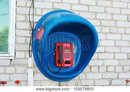 Red payphone in the blue booth on a white brick wall.