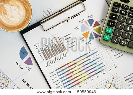 office desk working table with calculator business graph or analysis chart and calculator cup of coffee.Top view with copy space.Office supplies and gadgets concept.