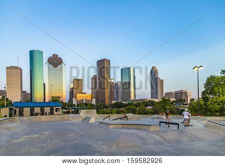 People Enjoy Riding Skateboard In  With The City Of Houston  As Background