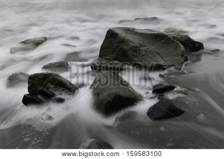 White water smoothly flows around rocks and sand at a beach Victoria British Columbia Canada