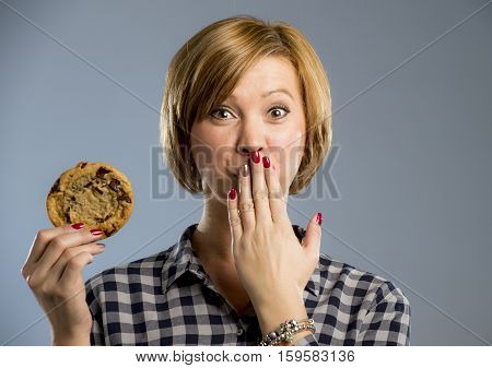 young blond cute and friendly caucasian woman in casual clothes holding big delicious chocolate cookie looking with temptation ready to not respect diet and go for sweet unhealthy snack