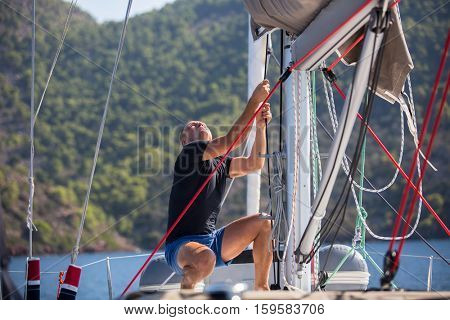 Man pulls the rope tuning the sails on the boat. Sailing ship during sea yacht race.