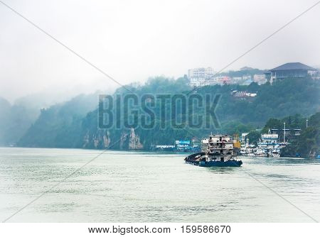 Cargo ship cruising on Yangtze river in rainy day