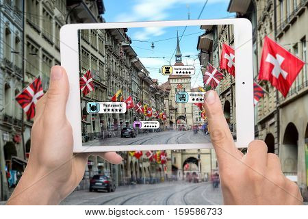 Hand holding smart phone use AR application to check relevant information about the spaces around customer. Bern City in background. Augmented reality marketing concept.