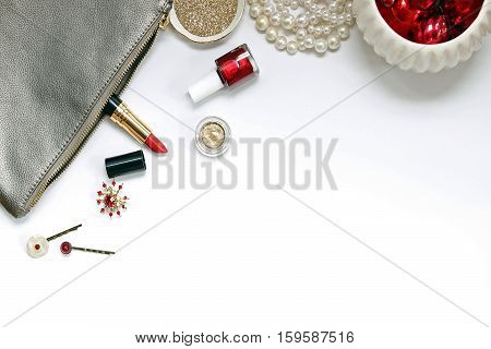 Over head flat lay view of a luxury vanity desk top. Silver, gold and red metallic. Cosmetics, jewelry, glitter, and ornaments. Open space for text.