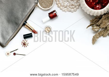Over head flat lay view of a luxury vanity desk top. Silver, gold and red metallic. Cosmetics, jewelry, glitter, ornaments, and glittered leaves. Open space for text.