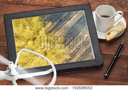 aerial photography concept - reviewing aerial pictures of trees and shadows on a digital tablet with a drone rotor and coffee, screen picture copyright by the photographer