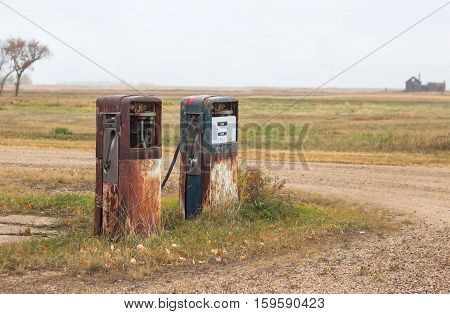 horizontal image of two rusty old abandoned gas pumps standing by themselves on a corner of the road.