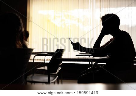 Silhouette of seriously middle edge man holding smartphone in meeting room or conference room. Phone with blank screen texting video calls holidays work using internet copy space.