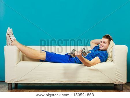 Relax after sport activity. Young man fit body relaxing on couch or having dreams of muscular body dumb bell in hand