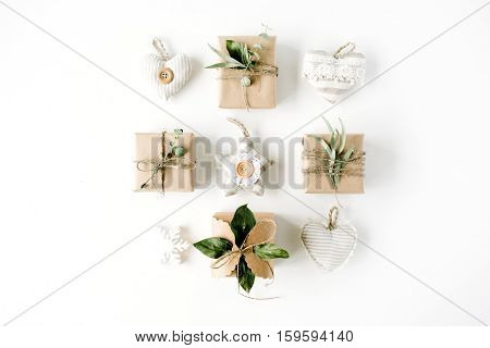 creative arrangement of handmade knitted christmas toys and craft boxes on white background. flat lay top view