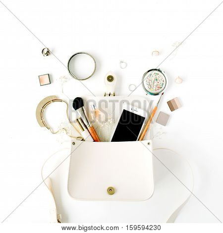 flat lay feminine arrangement with phone accessories purse cosmetics on white flat lay top view