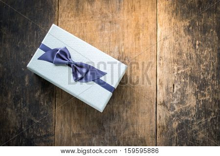 White colored gift box tied with blue bow on wooden background
