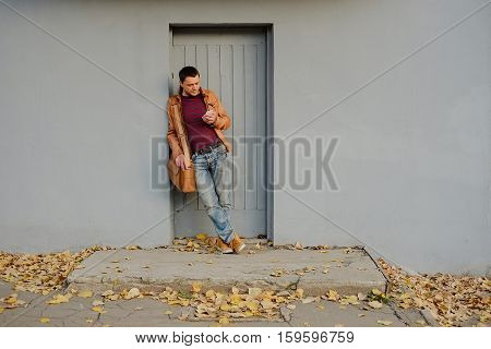 the guy with the phone in his hand standing at the wall fall under the feet of yellow leaves