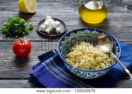 Ingredients for cooking tabbouleh salad with bulgur, tomato, parsley, lemon, olive oil and fresh goat cheese on wooden table background.