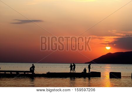 a group of fishermen on the pier sunset mountains in the background