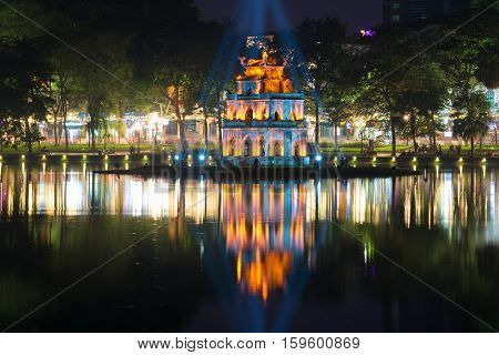 HANOI, VIETNAM - JANUARY 10, 2016: A tower of the Turtle against the background of the city embankment in a night landscape. The religious landmark of the city Hanoi, Vietnam