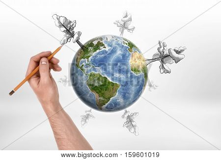 A man's hand drawing trees of different size with a pencil around the globe on the white background. Ecology and health. Creativity and art. Environmental issues. Elements of this image are furnished by NASA.