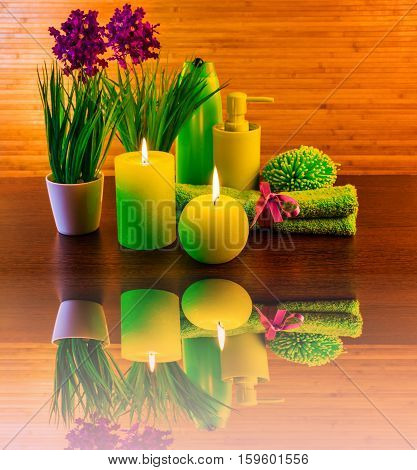 Green spa bath products concept with candles flowers towel with reflection