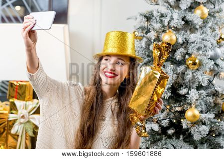 Young smiling woman in sweater and golden hat making selfie portrait with beautiful candy in decorated home interior with Christmas tree. Happy New Year concept