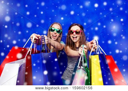 Glad Smiling Girls Showing Their Purchases For Christmas
