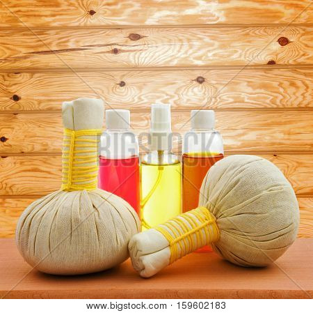 Concept of spa compress balls with bottles of aroma oil on wooden table and on wooden background