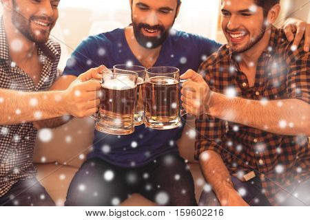 Three Happy Men Clinking With Glasses Of Beer On Christmas