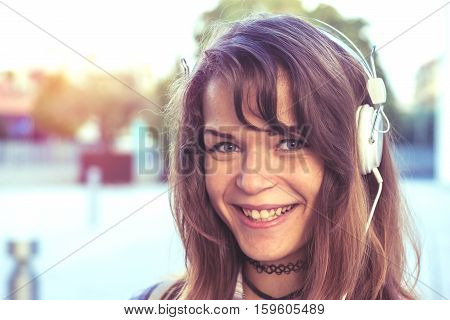 happy teenager woman with beautiful teeth smile listens to music using headphones. concept of positive attitude.