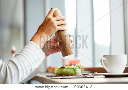 food, culinary, eating and people concept - woman hand with salt shaker seasoning brie cheese salad at restaurant or cafe