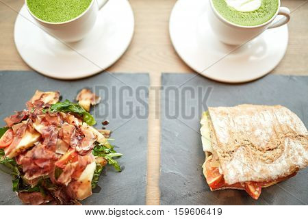food, dinner, haute cuisine and eating concept - prosciutto ham salad with panini sandwich on stone plates and cups of matcha green tea latte at restaurant