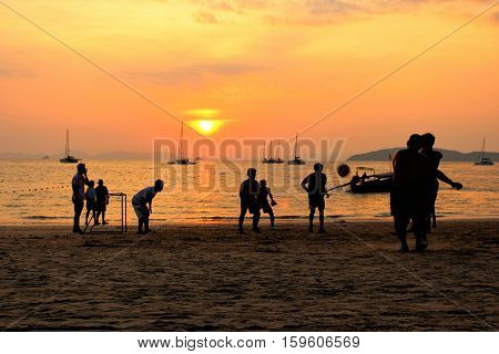 Friends playing football on the beach at sunset